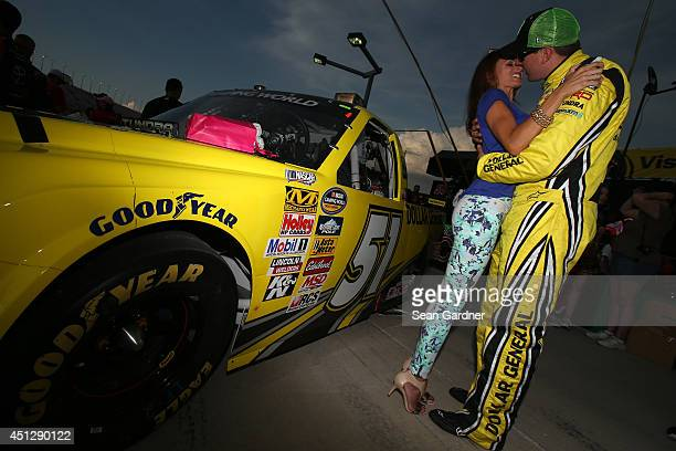 Kyle Busch driver of the Dollar General Toyota kisses his wife Samantha Busch before starting the NASCAR Camping World Series UNOH 225 at Kentucky...