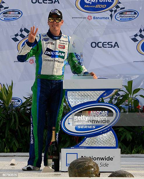 Kyle Busch driver of the Doosan Infracore Toyota poses with the trophy after winning the NASCAR Nationwide Series Corona Mexico 200 at Autodromo...