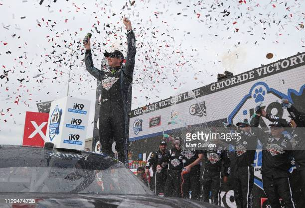 Kyle Busch driver of the Extreme Concepts/iK9 Toyota celebrates in Victory Lane after winning the NASCAR Xfinity Series iK9 Service Dog 200 at ISM...