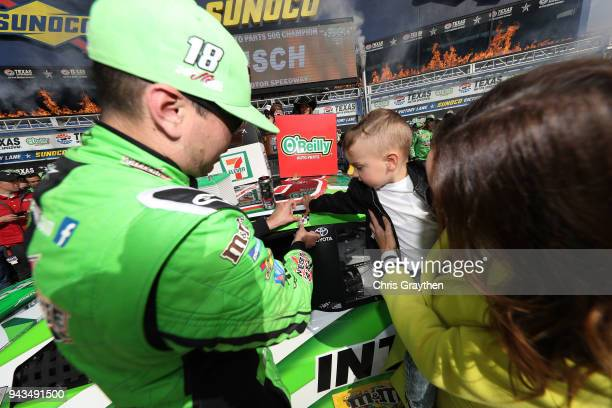 Kyle Busch driver of the Interstate Batteries Toyota affixes the winner's decal to his car in Victory Lane with his son Brexton and wife Samantha...