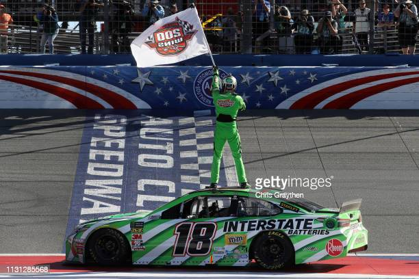 Kyle Busch, driver of the Interstate Batteries Toyota, celebrates after winning the Monster Energy NASCAR Cup Series Auto Club 400 and winning his...