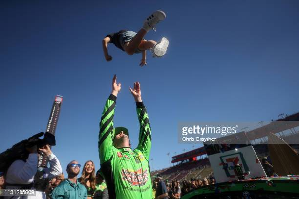 Kyle Busch driver of the Interstate Batteries Toyota celebrates by tossing his son Brexton in the air after winning the Monster Energy NASCAR Cup...