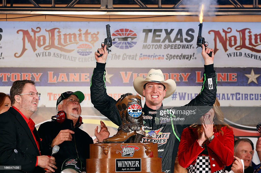 Kyle Busch, driver of the #18 Interstate Batteries Toyota, celebrates by shooting revolvers in Victory Lane as Texas Motor Speedway president Eddie Gossage (L) looks on after winning the NASCAR Sprint Cup Series NRA 500 at Texas Motor Speedway on April 13, 2013 in Fort Worth, Texas.