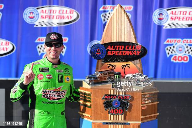 Kyle Busch driver of the Interstate Batteries Toyota celebrates in victory lane after winning the Monster Energy NASCAR Cup Series Auto Club 400 and...