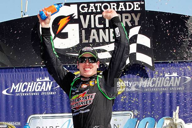 Kyle Busch driver of the Interstate Batteries Toyota celebrates in Victory Lane after winning the NASCAR Sprint Cup Series Pure Michigan 400 at...