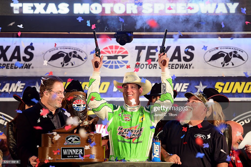 Kyle Busch, driver of the #18 Interstate Batteries Toyota, celebrates in Victory Lane after winning the NASCAR Sprint Cup Series Duck Commander 500 as Texas Motor Speedway President Eddie Gossage (L) and John Godwin of Duck Commander (R) look on at Texas Motor Speedway on April 9, 2016 in Fort Worth, Texas.