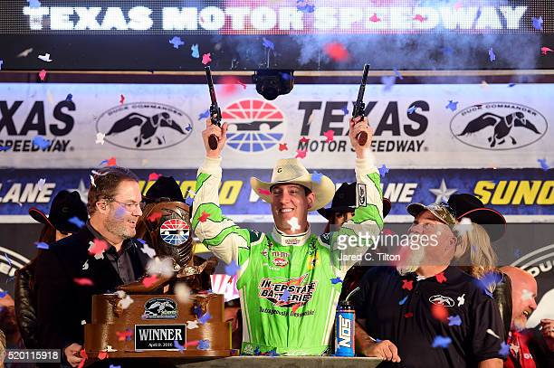 Kyle Busch driver of the Interstate Batteries Toyota celebrates in Victory Lane after winning the NASCAR Sprint Cup Series Duck Commander 500 as...