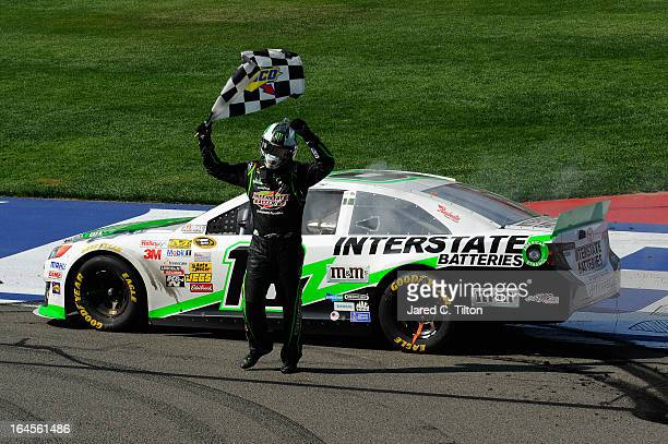 Kyle Busch driver of the Interstate Batteries Toyota celebrates with the checkered flag after winning the NASCAR Sprint Cup Series Auto Club 400 at...