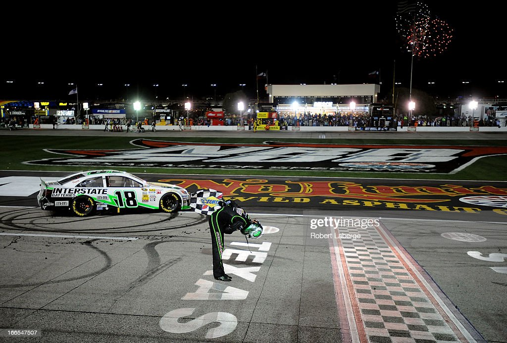 Kyle Busch, driver of the #18 Interstate Batteries Toyota, celebrates with the checkered flag after winning the NASCAR Sprint Cup Series NRA 500 at Texas Motor Speedway on April 13, 2013 in Fort Worth, Texas.