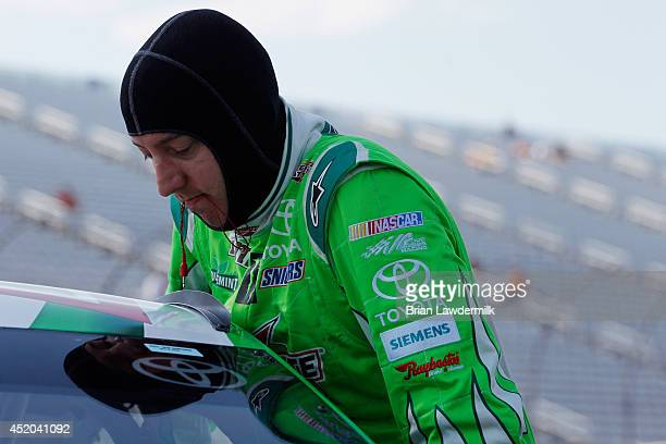 Kyle Busch, driver of the Interstate Batteries Toyota, climbs into his car during qualifying for the NASCAR Sprint Cup Series Camping World RV Sales...