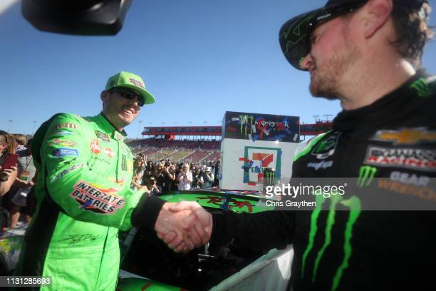 Kyle Busch driver of the Interstate Batteries Toyota is congratulated by his brother Kurt Busch driver of the Monster Energy Chevrolet after winning...