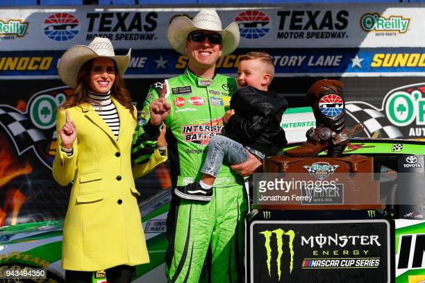 Kyle Busch driver of the Interstate Batteries Toyota poses in Victory Lane with his son Brexton and wife Samantha after winning the Monster Energy...