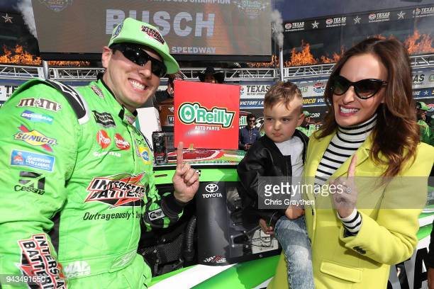 Kyle Busch driver of the Interstate Batteries Toyota poses with the winner's decal in Victory Lane with his son Brexton and wife Samantha after...