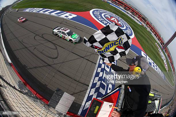 Kyle Busch, driver of the Interstate Batteries Toyota, takes the checkered flag to win the NASCAR Sprint Cup Series Auto Club 400 at Auto Club...