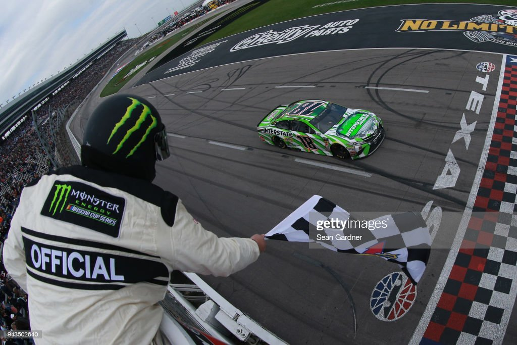 Kyle Busch, driver of the #18 Interstate Batteries Toyota, takes the checkered flag to win the Monster Energy NASCAR Cup Series O'Reilly Auto Parts 500 at Texas Motor Speedway on April 8, 2018 in Fort Worth, Texas.