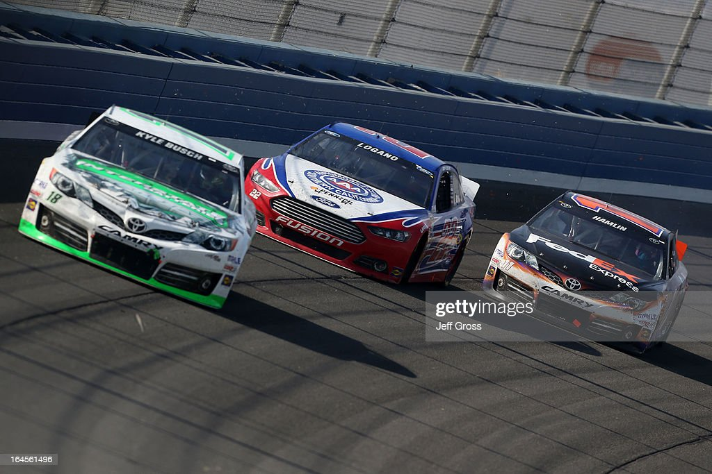 Kyle Busch, driver of the #18 Interstate Batteries Toyota, takes the lead as Joey Logano, driver of the #22 AAA Southern California Ford, collides with Denny Hamlin, driver of the #11 FedEx Express Toyota, on the the last lap during the NASCAR Sprint Cup Series Auto Club 400 at Auto Club Speedway on March 24, 2013 in Fontana, California.