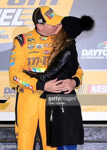 Kyle Busch driver of the MM's 75 Toyota celebrates in Victory Lane with his wife Samantha after winning the NASCAR Sprint Cup Series CanAm Duels at...