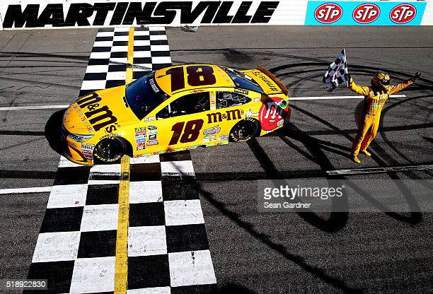 Kyle Busch driver of the MM's 75th Anniversary Toyota celebrates with the checkered flag after winning the NASCAR Sprint Cup Series STP 500 at...