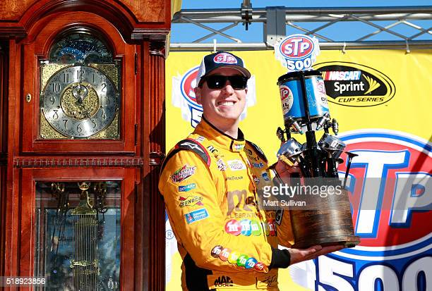 Kyle Busch driver of the MM's 75th Anniversary Toyota poses with the trophy in Victory Lane after winning the NASCAR Sprint Cup Series STP 500 at...