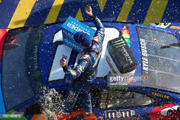 Kyle Busch driver of the MM's Caramel Toyota celebrates in Victory Lane after winning the Monster Energy NASCAR Cup Series Gander Outdoors 400 at...