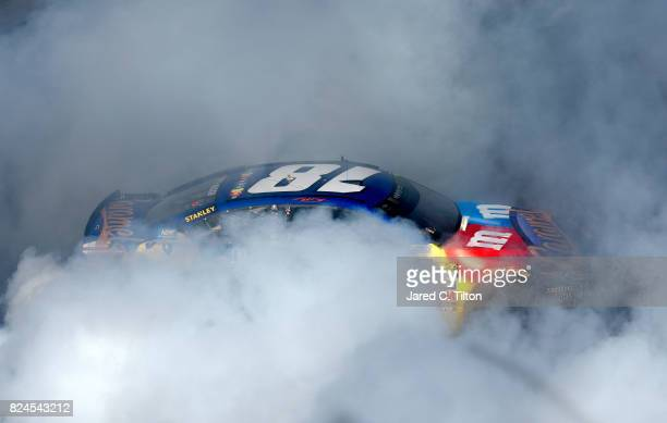 Kyle Busch driver of the MM's Caramel Toyota celebrates with a burnout after winning the Monster Energy NASCAR Cup Series Overton's 400 at Pocono...