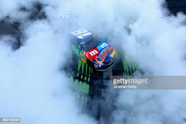 Kyle Busch driver of the MM's Caramel Toyota celebrates with a burnout after winning the Monster Energy NASCAR Cup Series ISM Connect 300 at New...