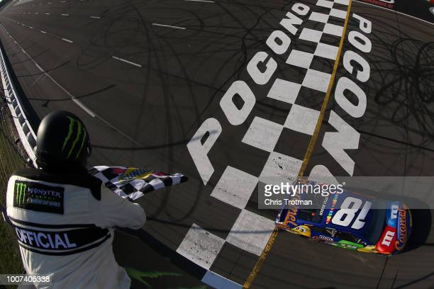 Kyle Busch driver of the MM's Caramel Toyota crosses the finish line to win the Monster Energy NASCAR Cup Series Gander Outdoors 400 at Pocono...