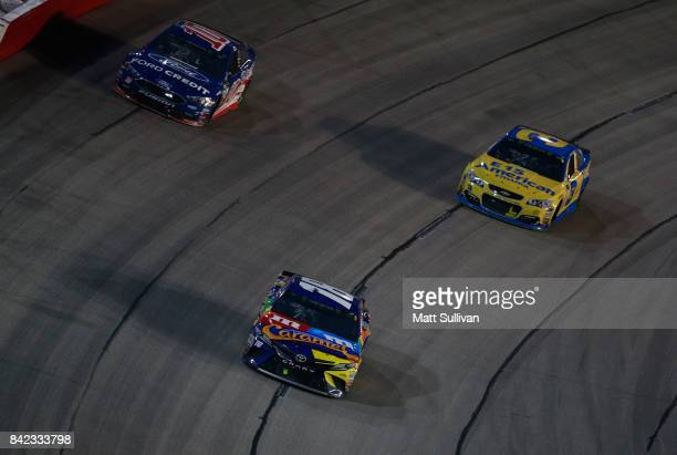 Kyle Busch driver of the MM's Caramel Toyota leads Austin Dillon driver of the American Ethanol Chevrolet and Danica Patrick driver of the Ford...