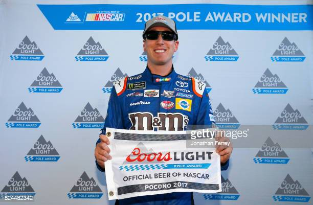 Kyle Busch driver of the MM's Caramel Toyota poses with the Coors Light Pole Award after qualifying in the pole position for the Monster Energy...