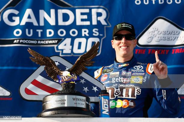 Kyle Busch driver of the MM's Caramel Toyota poses with the trophy in Victory Lane after winning the Monster Energy NASCAR Cup Series Gander Outdoors...