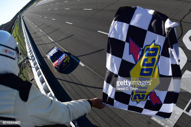 Kyle Busch driver of the MM's Caramel Toyota takes the checkered flag to win the Monster Energy NASCAR Cup Series Overton's 400 at Pocono Raceway on...