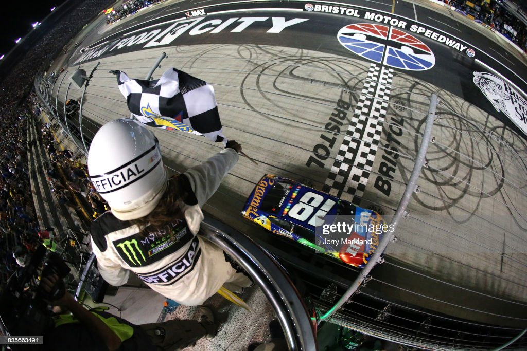 Kyle Busch, driver of the #18 M&M's Caramel Toyota, takes the checkered flag to win the Monster Energy NASCAR Cup Series Bass Pro Shops NRA Night Race at Bristol Motor Speedway on August 19, 2017 in Bristol, Tennessee.