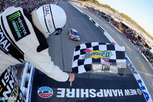 Kyle Busch driver of the MM's Caramel Toyota takes the checkered flag to win the Monster Energy NASCAR Cup Series ISM Connect 300 at New Hampshire...