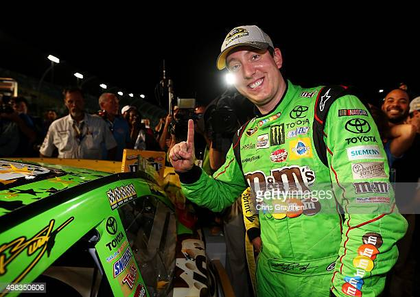 Kyle Busch driver of the MM's Crispy Toyota affixes the winner's decal to his car in Victory Lane after winning the series championship and the...
