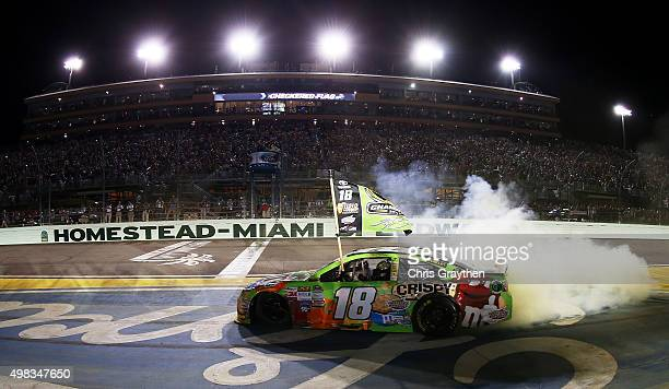 Kyle Busch, driver of the M&M's Crispy Toyota, celebrates winning the series championship and the race with a burnout after the NASCAR Sprint Cup...