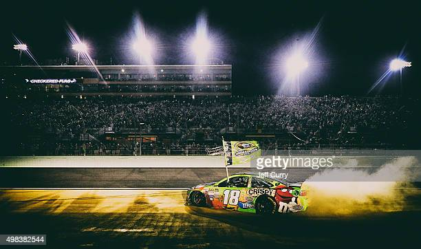 Kyle Busch driver of the MM's Crispy Toyota celebrates with a burnout after winning the series championship and the NASCAR Sprint Cup Series Ford...
