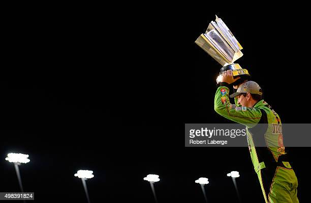 Kyle Busch driver of the MM's Crispy Toyota poses with the trophy in Victory Lane after winning the series championship and the NASCAR Sprint Cup...