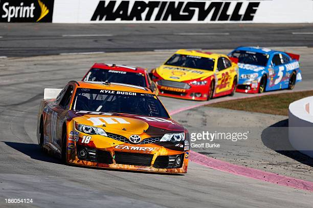 kyle busch driver of the mms halloween toyota leads a group of cars during the nascar