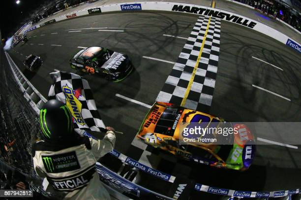 Kyle Busch driver of the MM's Halloween Toyota takes the checkered flag to win the Monster Energy NASCAR Cup Series First Data 500 at Martinsville...