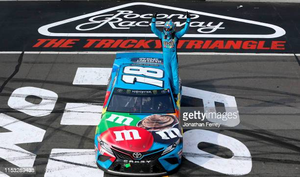 Kyle Busch driver of the MM's Hazelnut Toyota celebrates winning the Monster Energy NASCAR Cup Series Pocono 400 at Pocono Raceway on June 02 2019 in...