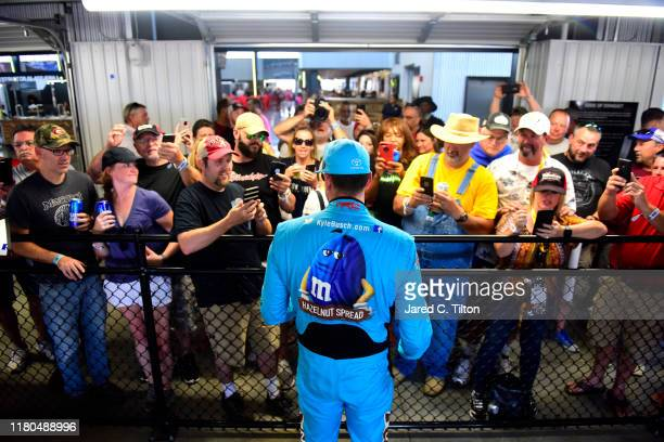 Kyle Busch driver of the MM's Hazelnut Toyota signs autographs for fans in the garage area during practice for the Monster Energy NASCAR Cup Series...