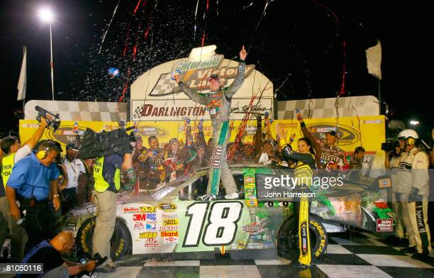 Kyle Busch, driver of the M&M's Indiana Jones Toyota, celebrates in victory lane after winning the NASCAR Sprint Cup Series Dodge Challenger 500 on...