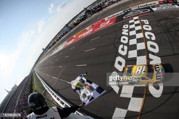 Kyle Busch, driver of the M&M's Mini's Toyota, takes the checkered flag to win the NASCAR Cup Series Explore the Pocono Mountains 350 at Pocono...
