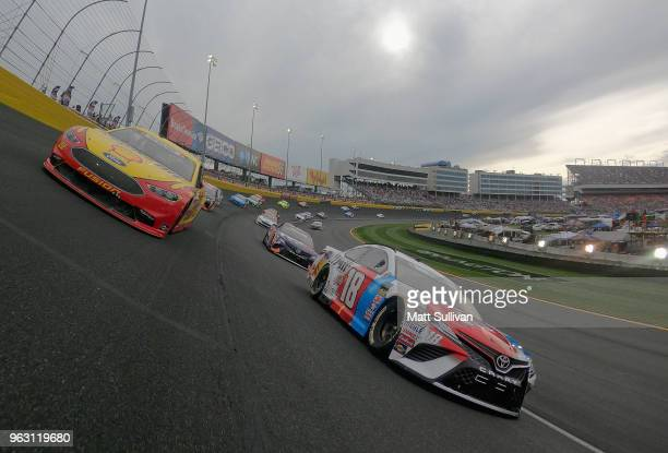 Kyle Busch, driver of the M&M's Red White & Blue Toyota, and Joey Logano, driver of the Shell Pennzoil Ford, lead the field during a pace lap prior...