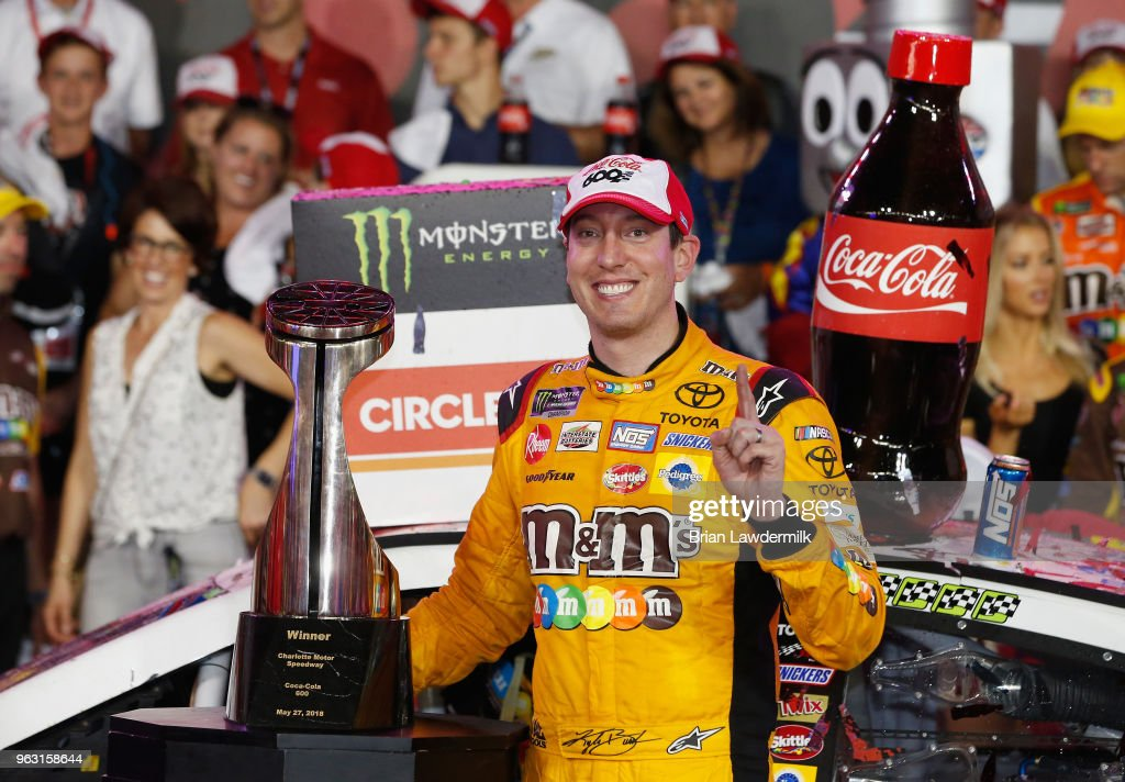 Kyle Busch, driver of the #18 M&M's Red White & Blue Toyota, poses with the trophy after winning the Monster Energy NASCAR Cup Series Coca-Cola 600 at Charlotte Motor Speedway on May 27, 2018 in Charlotte, North Carolina.