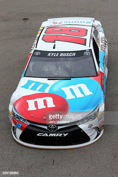Kyle Busch driver of the MM's RWB Toyota drives through the garage area during practice for the NASCAR Sprint Cup Series FireKeepers Casino 400 at...
