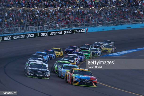 Kyle Busch driver of the MM's Toyota and Aric Almirola driver of the Smithfield Ford lead the field to a restart during the Monster Energy NASCAR Cup...