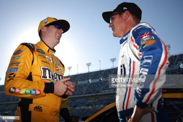 Kyle Busch driver of the MM's Toyota and Clint Bowyer driver of the Mobil 1 Ford stand on the grid during qualifying for the Monster Energy NASCAR...