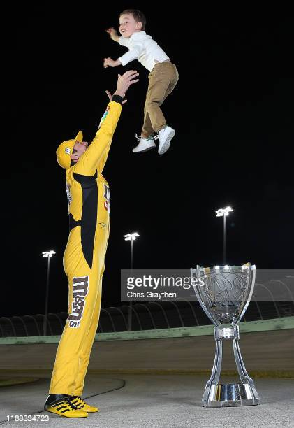 Kyle Busch, driver of the M&M's Toyota and his son Brexton pose with the trophy after winning the Monster Energy NASCAR Cup Series Championship at...