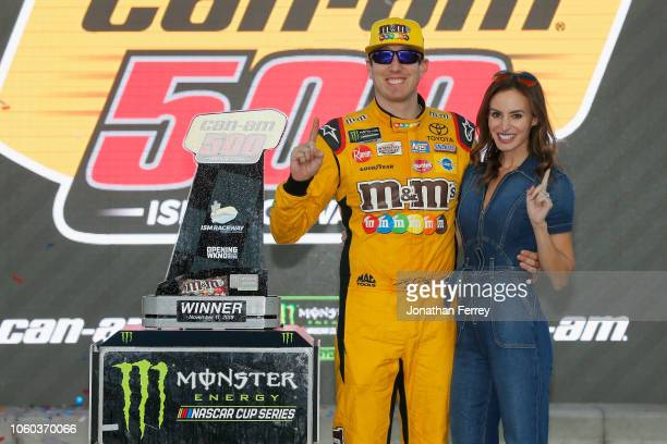 Kyle Busch driver of the MM's Toyota and his wife Samantha pose with the trophy in Victory Lane after winning the Monster Energy NASCAR Cup Series...